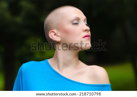 Happy young cancer survivor after successful chemotherapy enjoying day in the nature. - stock photo