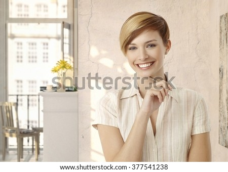 Happy young casual blonde caucasian housewife at vintage home. Smiling, looking at camera, pen in hand. Copyspace. - stock photo