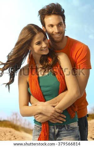 Happy young casual caucasian romantic couple embracing outdoors. Smiling, holding hands, standing. - stock photo