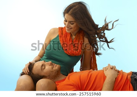 Happy young casual caucasian romantic couple resting with man in lap of girlfriend. Smiling, eyes closed, caressing, relaxing outdoor. Copyspace. - stock photo