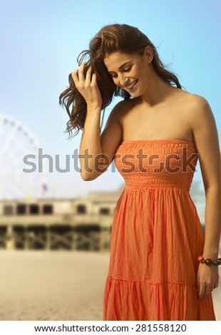 Happy young casual caucasian woman standing at the sandy summer beach. looking down. Smiling, copyspace. - stock photo