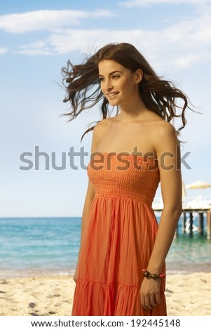 Happy young casual caucasian woman standing at the sandy summer beach. Smiling, copyspace. - stock photo