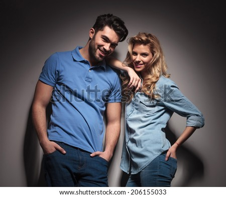happy young casual couple laughing together in studio