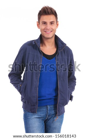 happy young casual man standing with hands in his pockets on white background