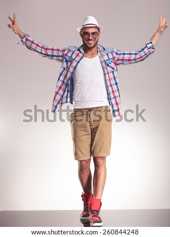 Happy young casual man walking while holding his hands up celebrating a victory. - stock photo