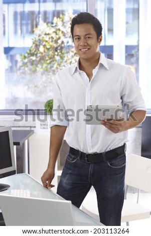 Happy young casual office worker holding tablet computer, smiling, looking at camera. - stock photo