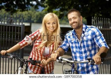 Happy young casual woman and man with bicycle outdoor, smiling, looking at camera, standing, married couple. - stock photo