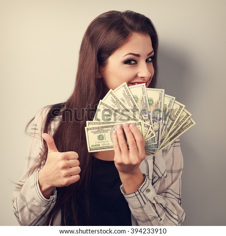 Happy young casual woman holding dollars and showing thumb up sign. Toned portrait