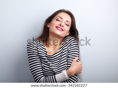 Happy young casual woman hugging herself with natural emotional enjoying face. Love concept by yourself