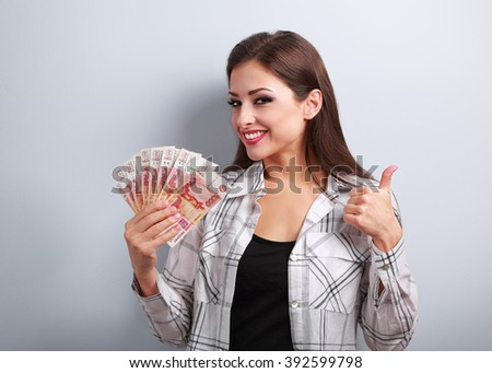 Happy young casual woman in glasses holding roubles and showing thumb up sign with toothy smiling on blue background - stock photo