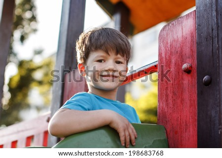Happy young caucasian boy smile on slide at outdoor, little kid.