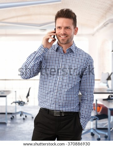 Happy young caucasian businessman on the phone in modern office. - stock photo