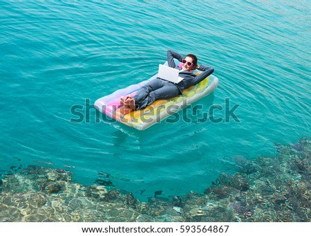 Happy young Caucasian businesswoman wearing formal suit and sunglasses floating on lilo with laptop, looking at camera and smiling. Businesswoman resting at seaside on vacation