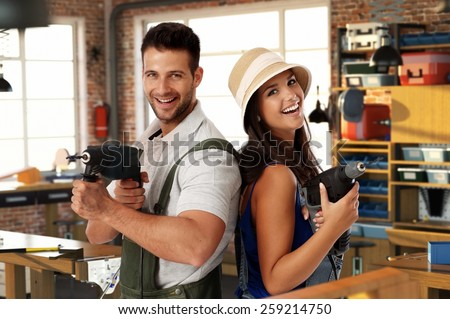 Happy young caucasian casual couple having fun at home workshop. Smiling, looking at camera, holding power drill in hand, standing. Handsome man, attractive female. Do it yourself.