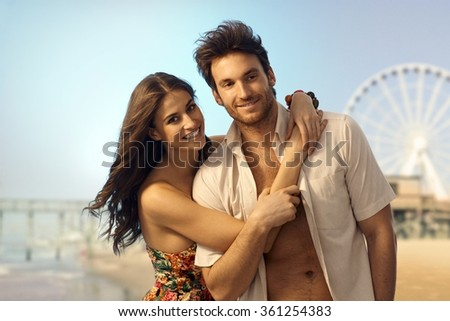 Happy young caucasian couple at sandy summer holiday beach. Smiling looking at camera, copyspace. Handsome bristly man.