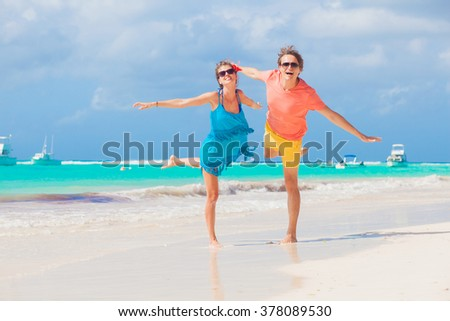 happy young caucasian couple in sunglasses enjoying their time on beach - stock photo
