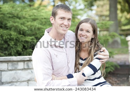 Happy young caucasian couple sitting at the park both hugging and smiling. - stock photo