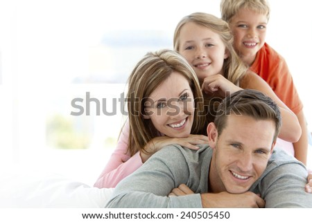 Happy young Caucasian family making a human pyramid