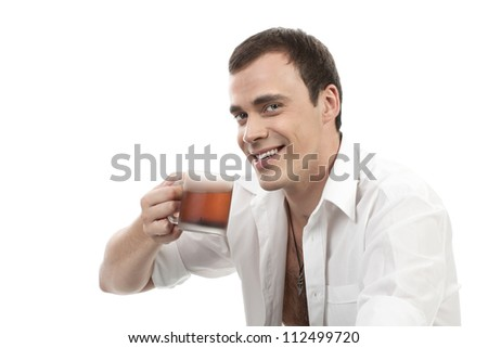 Happy young caucasian guy having a cup of tea isolated on white - stock photo