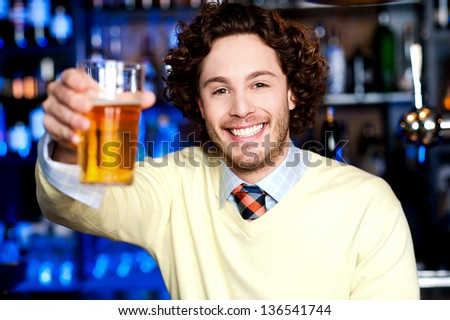 Happy young caucasian guy offering you beer glass...Cheers! - stock photo