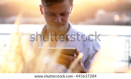 happy young caucasian man using tablet computer browsing the web online. urban lifestyle portrait of student  - stock photo