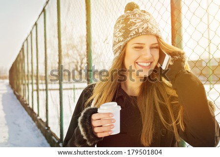 Happy young Caucasian teenage woman talking on the phone laughing holding a takeaway coffee cup smiling. Outdoors winter portrait of beautiful teenage girl speaking on the phone. - stock photo
