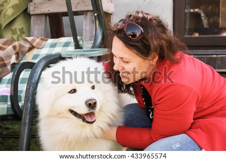 Happy young Caucasian woman and white fluffy Samoyed dog - stock photo