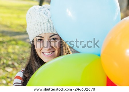 Happy Young Caucasian Woman holding colorful balloons. - stock photo