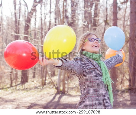 Happy Young Caucasian Woman holding colorful balloons at beautiful sunny day in nature.Winter autumn season outdoor. - stock photo