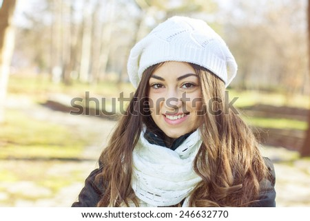 Happy Young Caucasian Woman spending free time in the park.Weather conditions between autumn and winter.