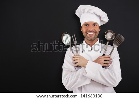Happy young chef with cooking equipment - stock photo