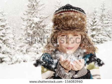 Happy young child blowing snowflakes in white winter snowy landscape - stock photo