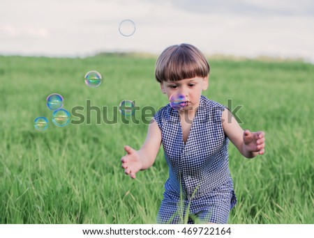 happy young  child have fun on meadow with soap bubbles