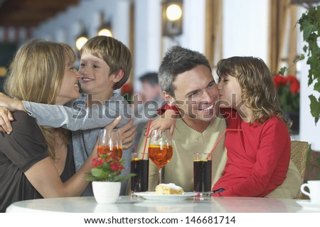 Happy young children embracing parents at restaurant table