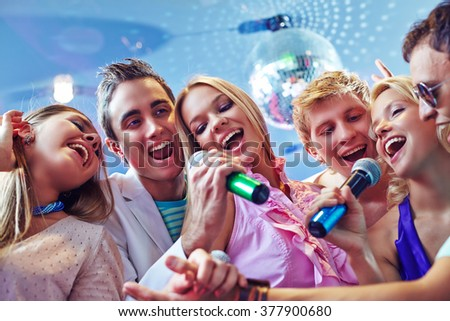 Happy young clubbers singing karaoke - stock photo