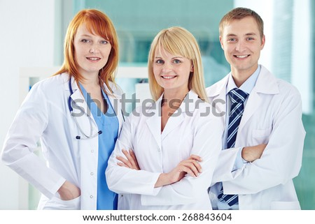 Happy young colleagues in white coats looking at camera - stock photo