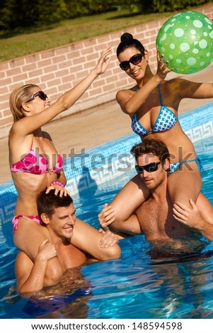 Happy young companionship having fun in outdoor pool at summertime. - stock photo