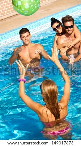 Happy young companionship having summer fun in swimming pool.