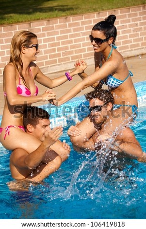 Happy young companionship having summer fun in swimming pool outdoor. - stock photo