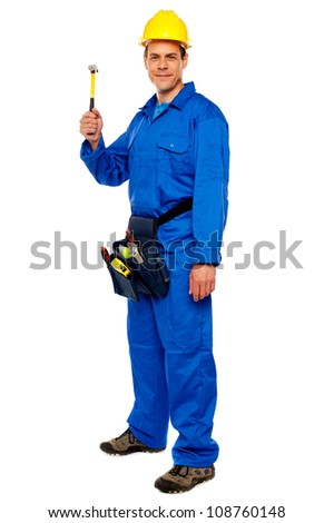 Happy young construction worker holding hammer and carrying tools bag