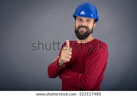 Happy young construction worker with hardhat showing ok sign over gray background - stock photo