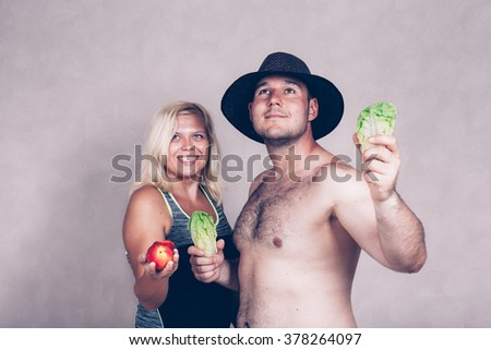 Happy young corpulent couple holding lettuce and nectarine.