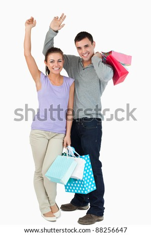 Happy young couple after shopping against a white background