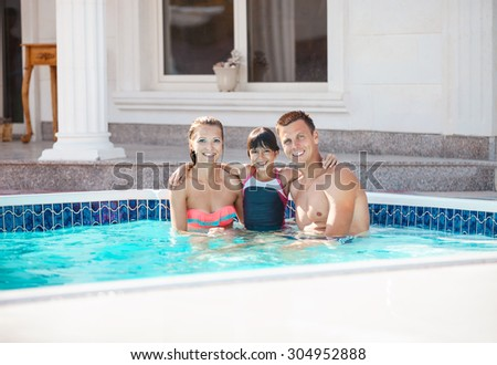Happy young couple and daughter in swimming pool near luxury villa