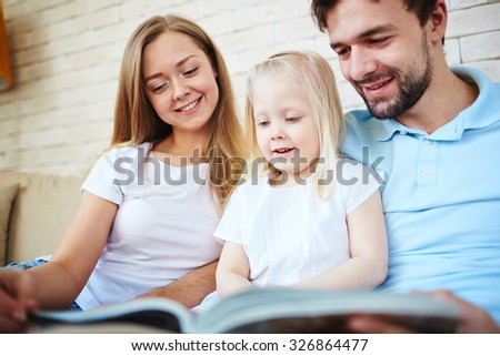Happy young couple and their daughter reading at home