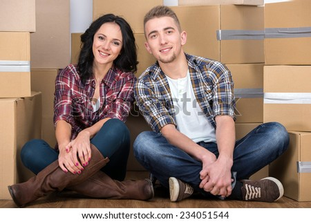 Happy young couple are moving in new home. Man and woman are sitting on the floor. - stock photo