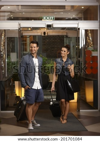 Happy young couple arriving at hotel with suitcases. - stock photo