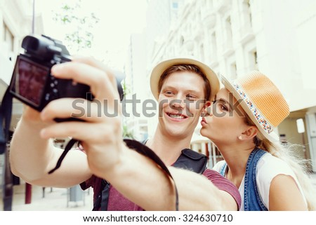 Happy young couple as tourists with a camera - stock photo