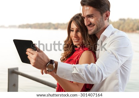 Happy young couple at the river with tablet - stock photo