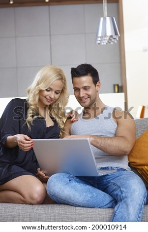 Happy young couple browsing internet at home, sitting on couch, smiling happy.